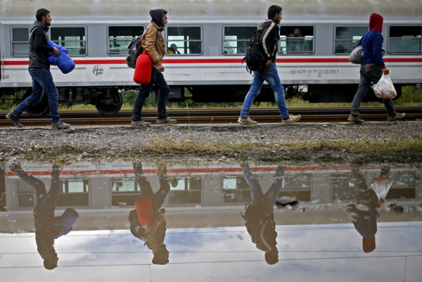 Migrants walk to board a train at the railway station in Tovarnik