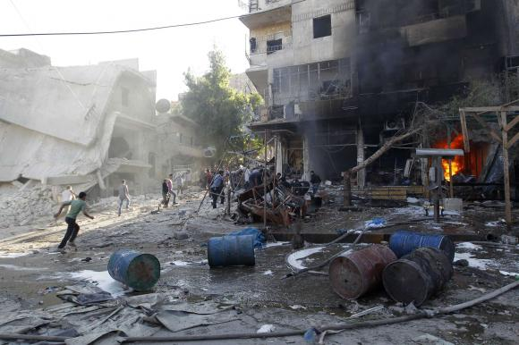 Residents run after, according to activists, two barrel bombs were thrown by forces loyal to Syria's president Al-Assad in Aleppo