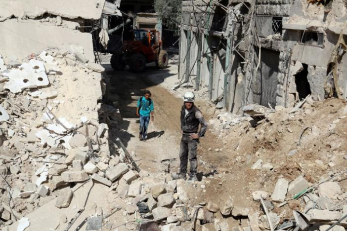 Civil defence members and men inspect a site damaged after an airstrike in the besieged rebel-held al-Qaterji neighbourhood of Aleppo