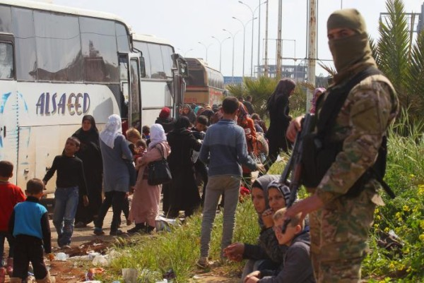 A rebel fighter stands near buses carrying people that were evacuated from the two villages of Kefraya and al-Foua, after a stall in an agreement between rebels and Syria's army, at insurgent-held al-Rashideen
