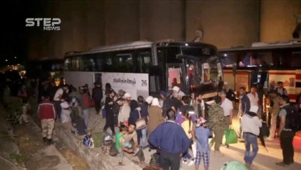 A still image taken from a video posted to a social media website shows people gathering near buses in what is said to be Qalaat al-Madiq, Hama province