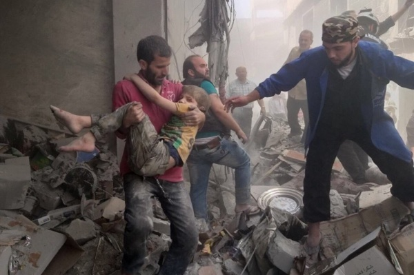 A man carries a wounded victim of pro-Assad bombing on Ariha, Syria, May 27, 2018