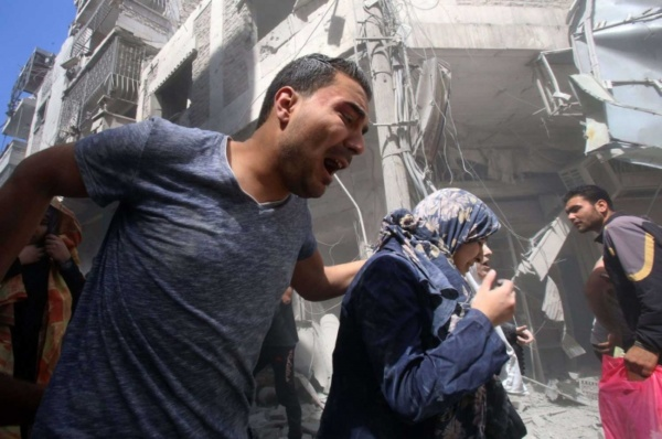 A man leads a woman await from site of pro-Assad bombing in Ariha, Idlib Province, Syria, May 27, 2019