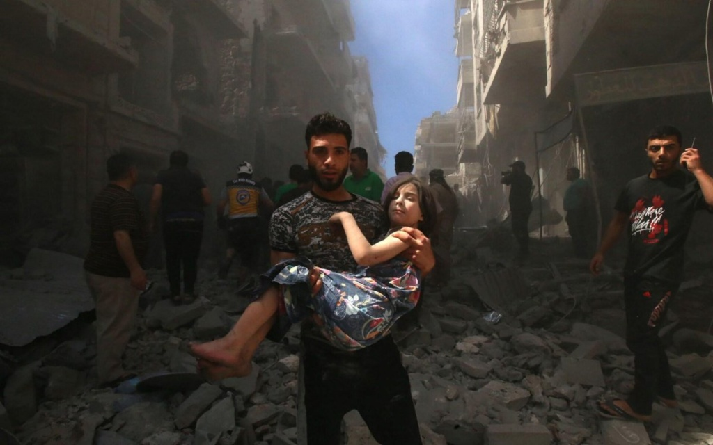 A man carries a girl await from site of pro-Assad attack, Idlib Province, Syria, May 2019