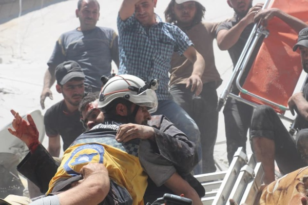White Helmets volunteer holds a man rescued after pro-Assad bombing of Idlib Province, Syria, May 27, 2019