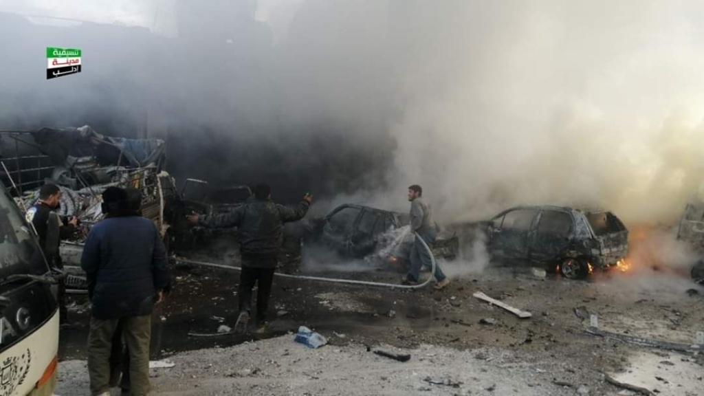 Men try to extinguish a fire amid burned vehicles after Russian-regime bombing of Idlib Province, northwest Syria, January 15, 2020