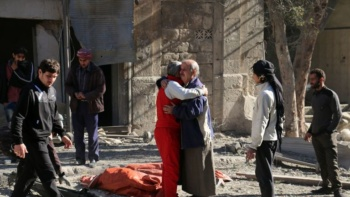 Residents comfort each other following an airstrike on east Aleppo's Bab al-Nayrab district in November 2016, weeks before reoccupation by pro-Assad forces